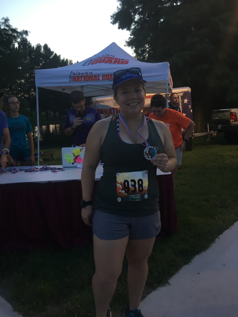 Vanessa Junkin wearing running clothes and standing with medal around neck and holding it. A tent is in the background.