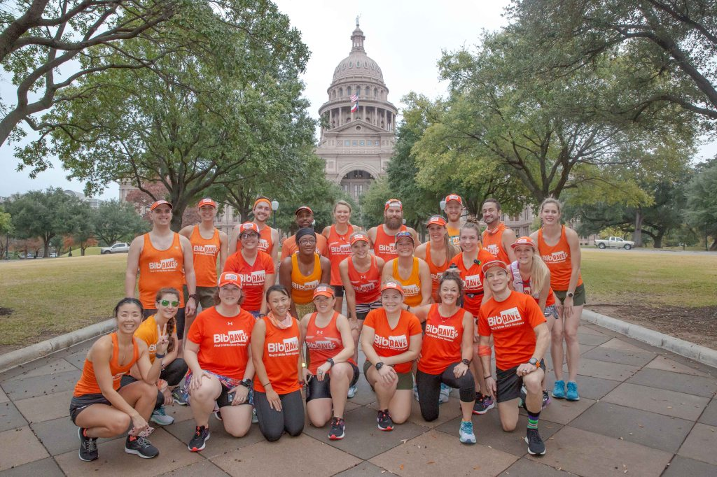 Group of BibRave Pros and Team BibRave pose in front of the Texas State Capitol building.