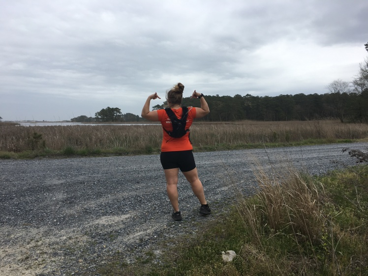 Vanessa Junkin, facing away from the camera, shows the Orange Mud Gear Vest Pro on a gravel road at the Assawoman Wildlife Area.