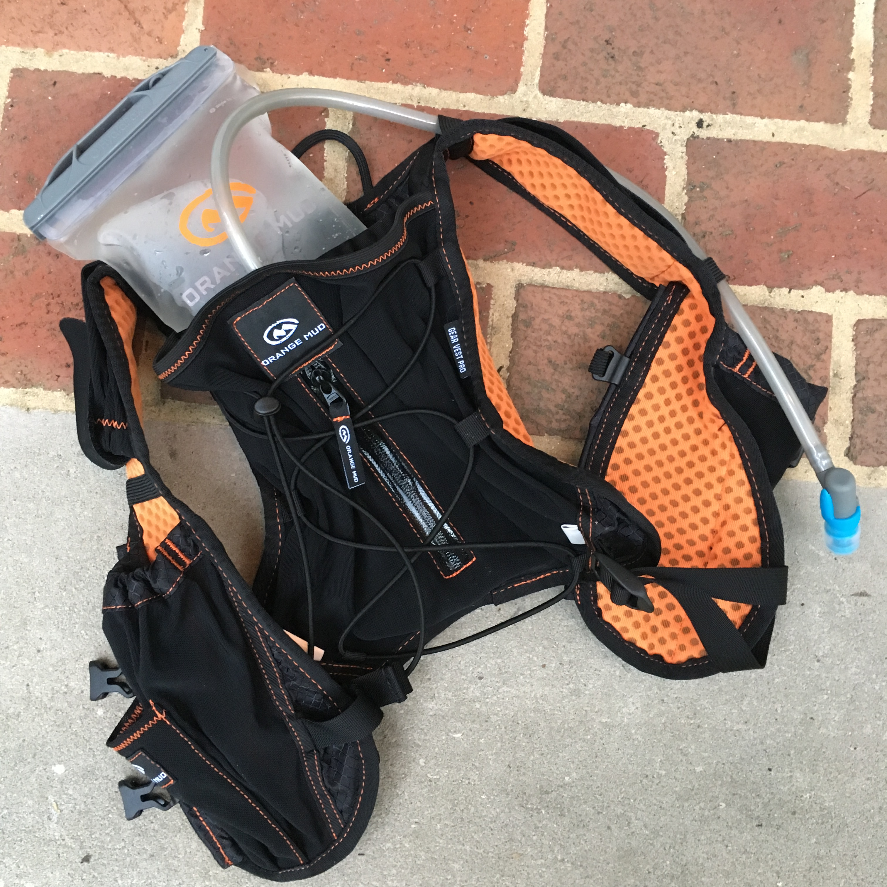 Orange Mud Gear Vest Pro, showing bladder holding water, against brick/concrete background.