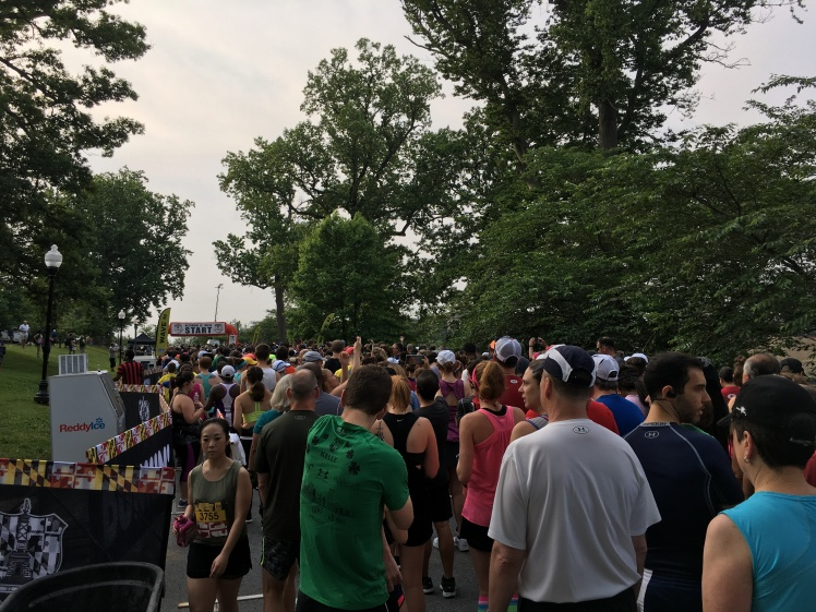 Starting corral for the Baltimore 10 Miler, showing large group of people and starting arch.
