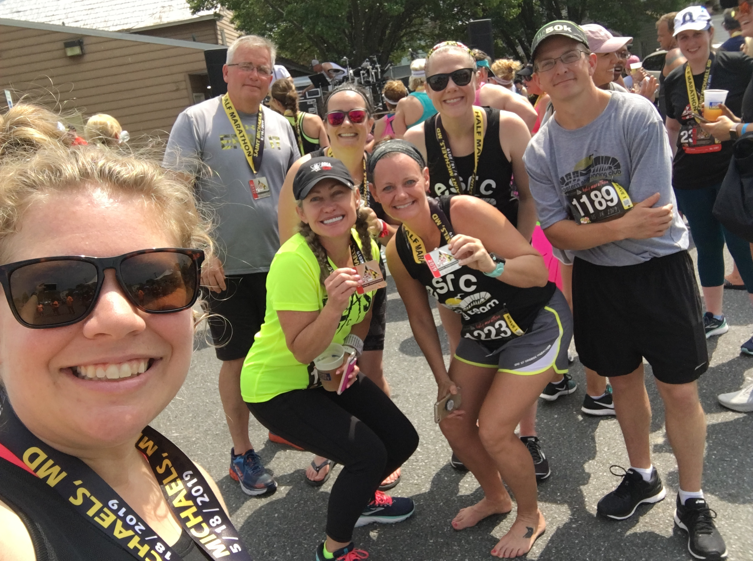 Eastern Shore Running Club members in a selfie taken by Vanessa Junkin. People are holding finisher medals.