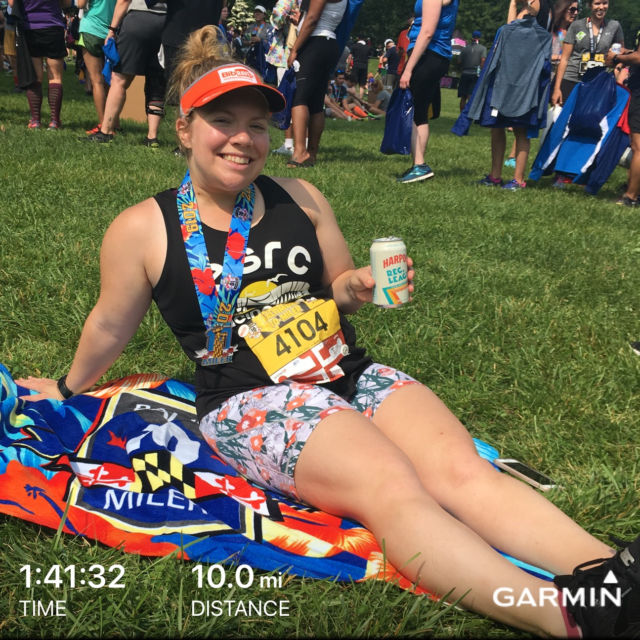 Vanessa relaxing on beach towel with beer after Baltimore 10 Miler.