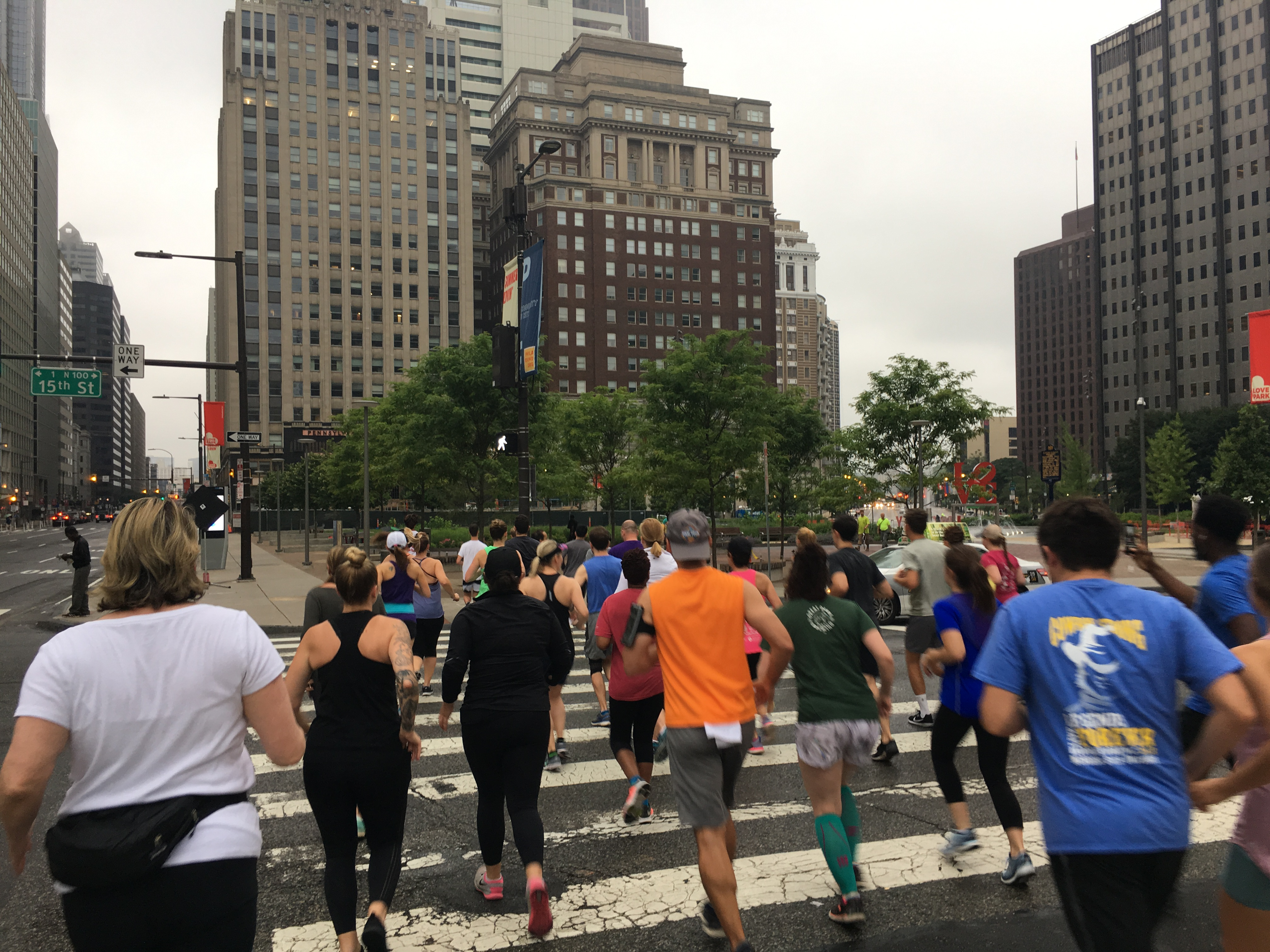 Runners cross a crosswalk in Philadelphia.
