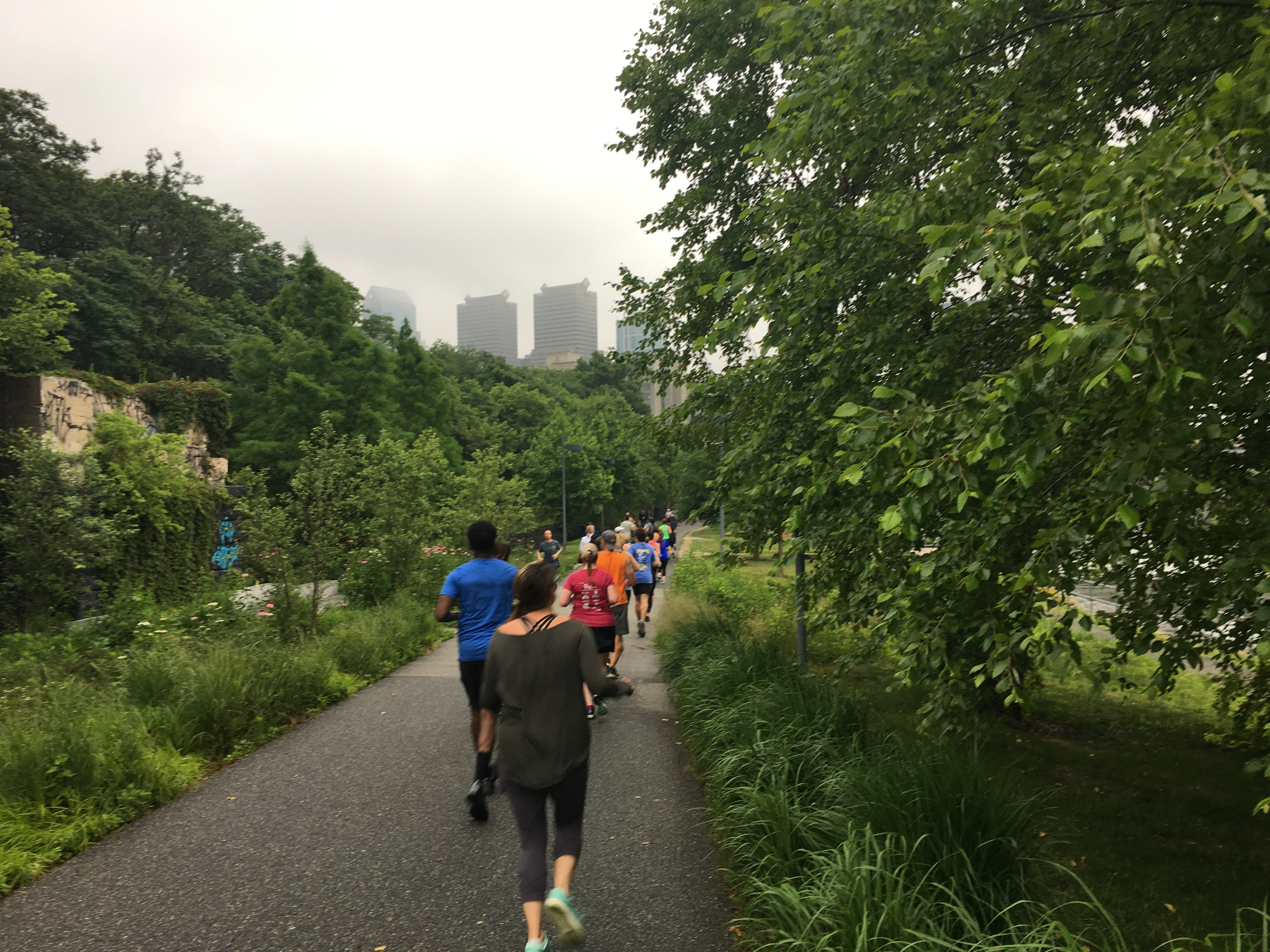 Runners on Schuylkill River Trail with some skyscrapers in the distance and trees on both sides.