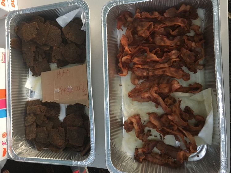 Scrapple, left, and bacon in foil trays.