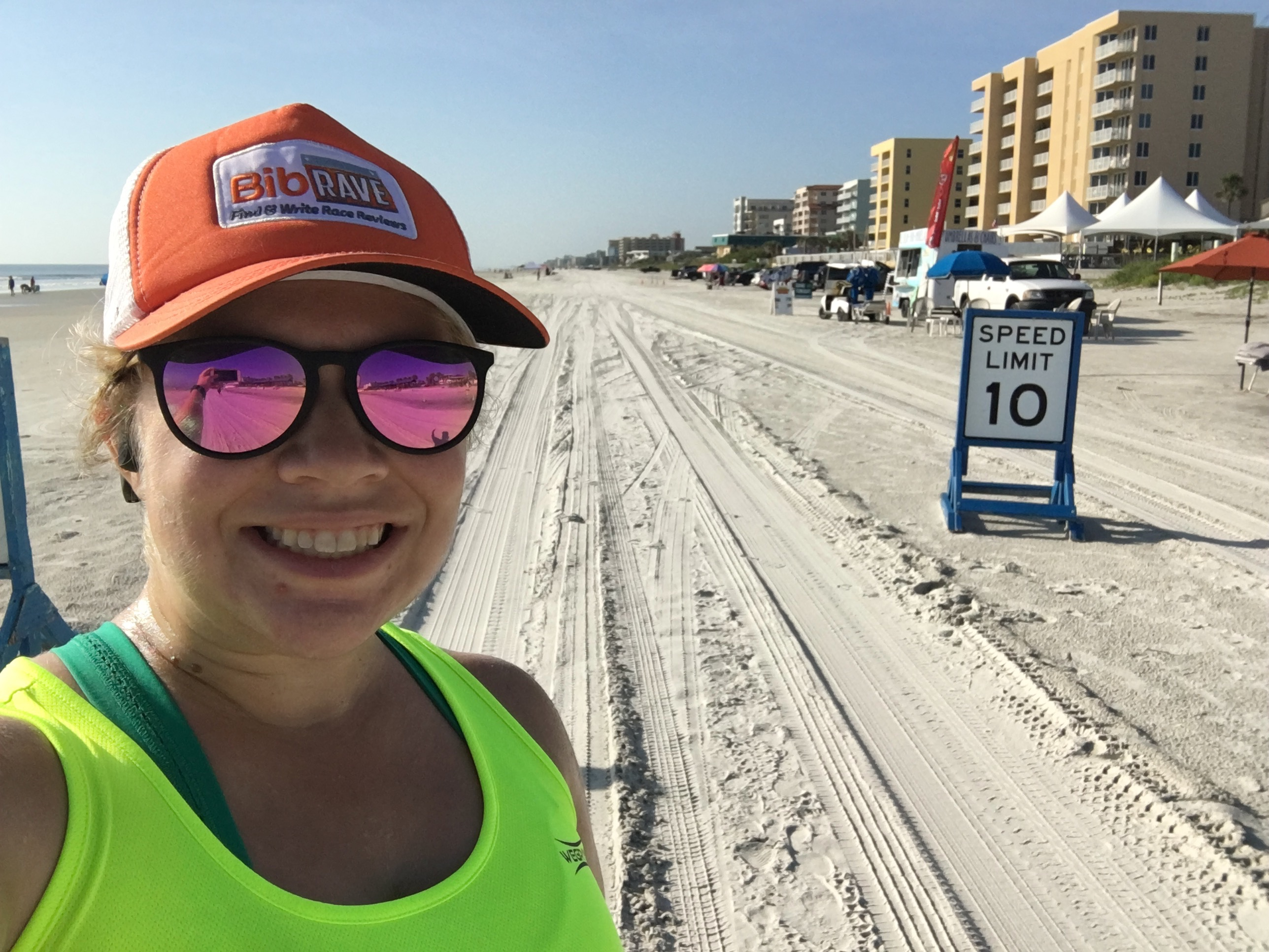 "Vanessa takes a selfie on the beach with a ""Speed Limit 10"" sign."