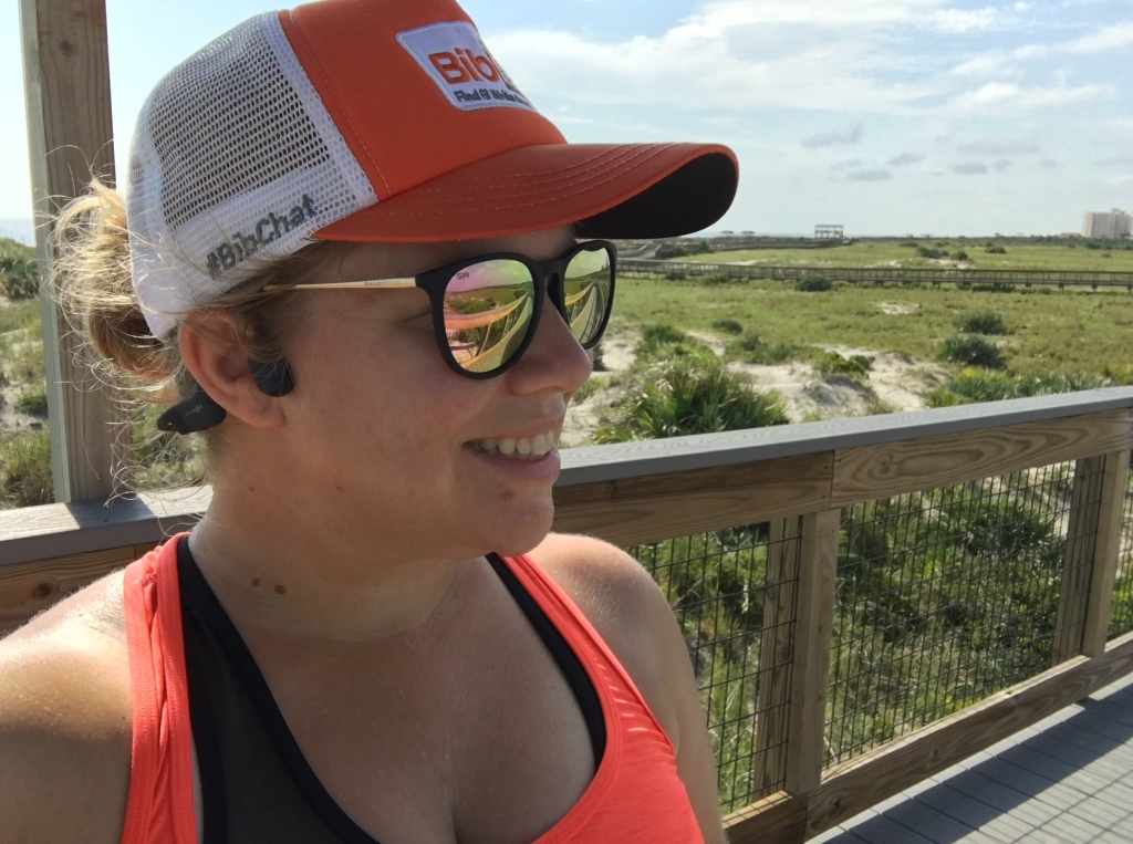 Vanessa Junkin at a scenic spot in Florida wearing the AfterShokz Aeropex, Shady Rays sunglasses and a BibRave hat.
