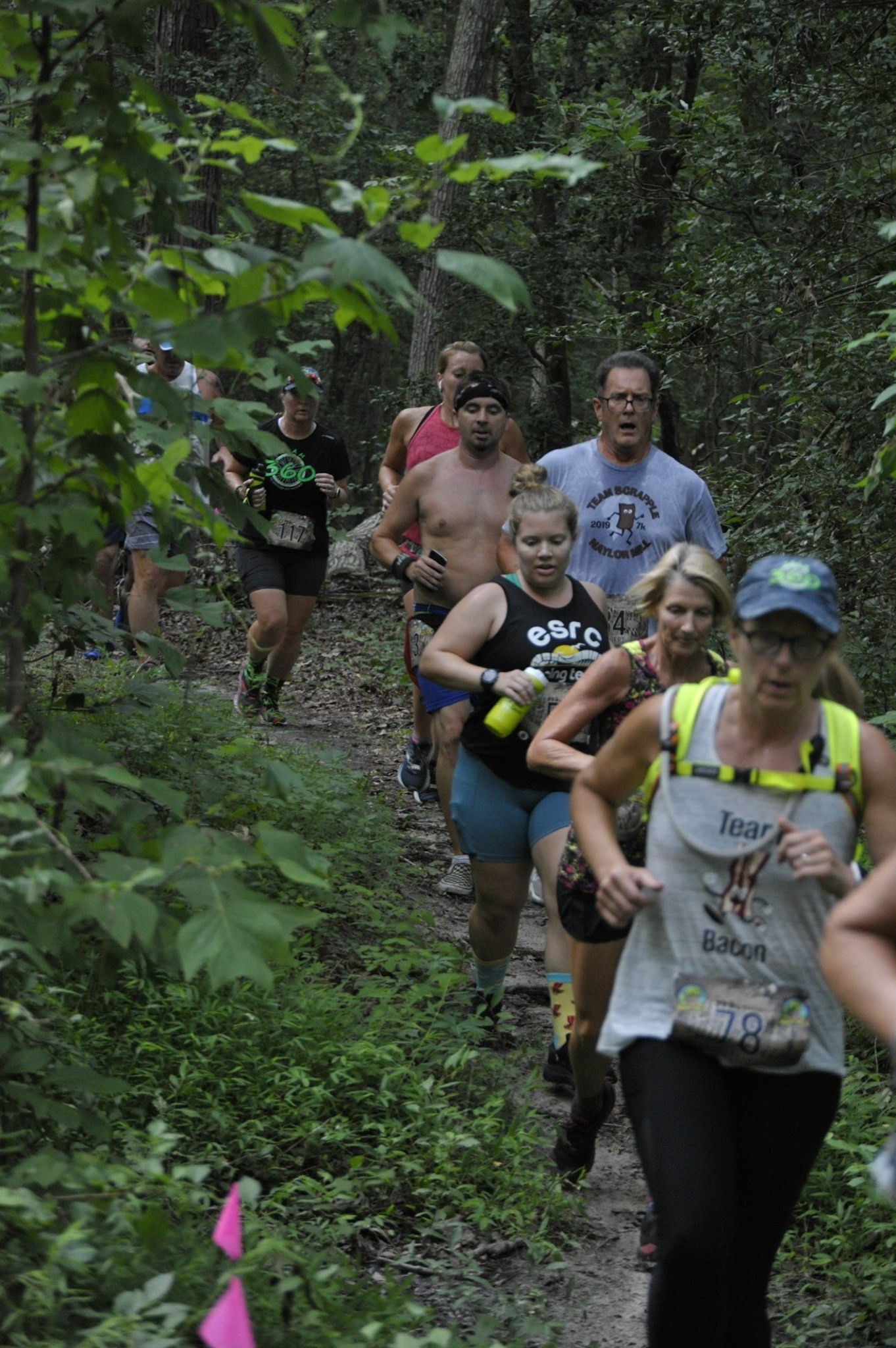 Vanessa and a group of runners run on a trail at the Naylor Mill 7K.