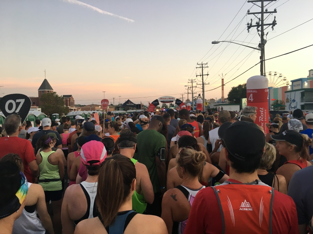 Large group of runners in the corral facing the starting line.