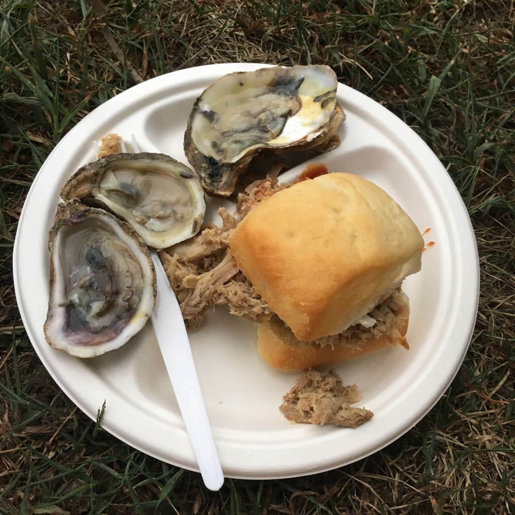 Oysters and a barbecue sandwich on a white plate.
