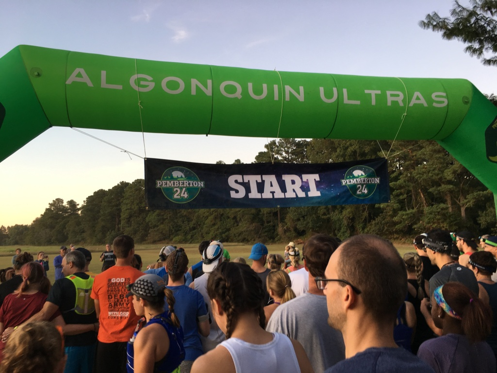 "Runners crowd underneath an ""Algonquin Ultras"" inflatable arch with a ""Start"" banner underneath."