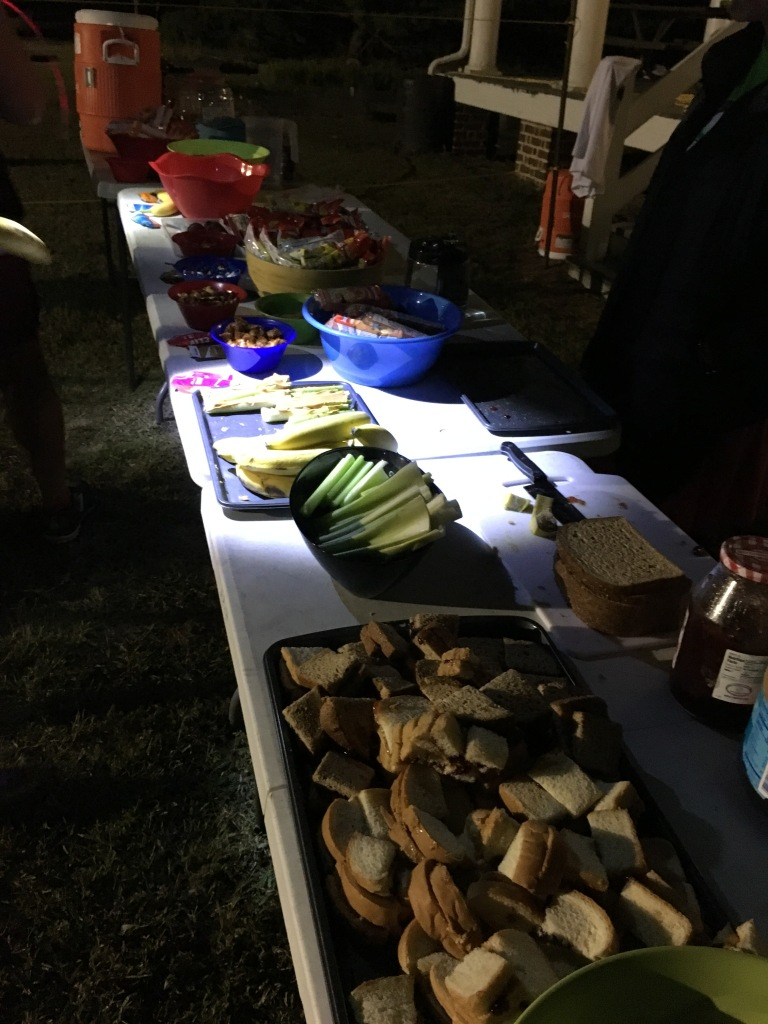 Various types of food at an aid station on tables — peanut butter and jelly, celery, snacks and more.