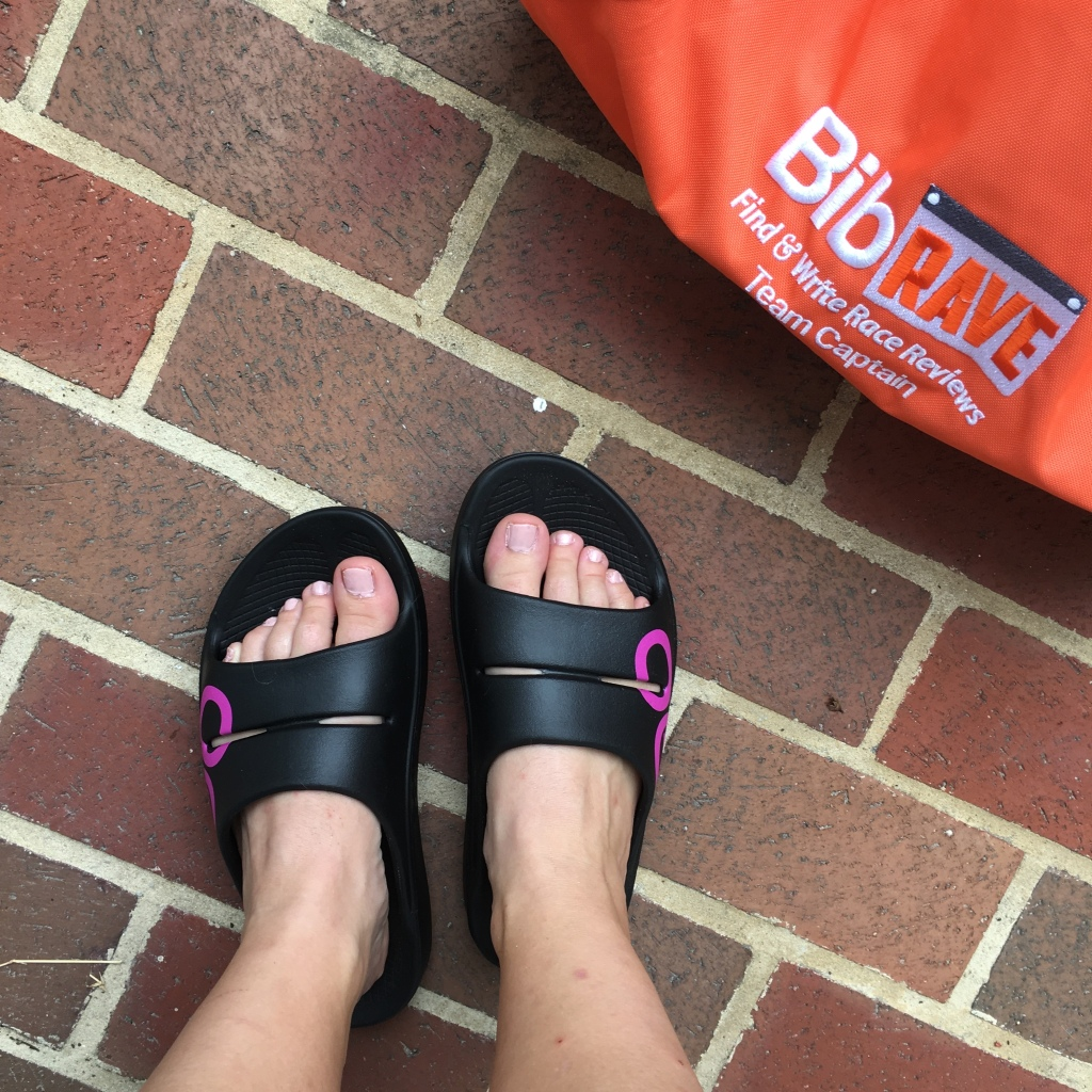 Vanessa's feet in the OOFOS on a brick background with a view of an orange BibRave bag.