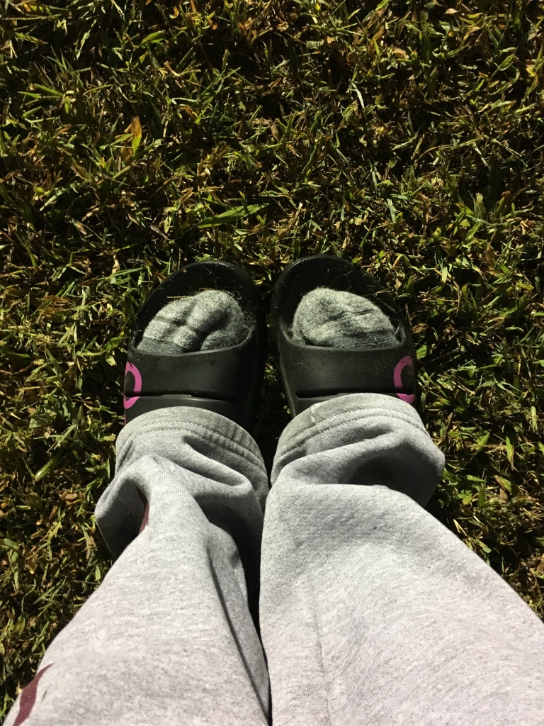 View of Vanessa's feet in socks in the OOFOS slides.