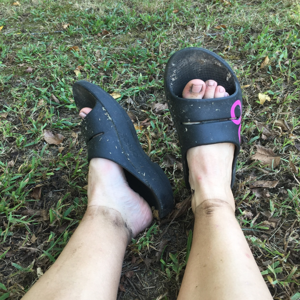 Vanessa's dirty feet in the OOFOS slides.