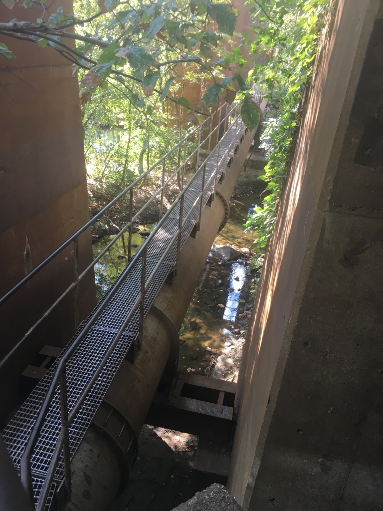 A path made of grates above a pipeline is shown from above.