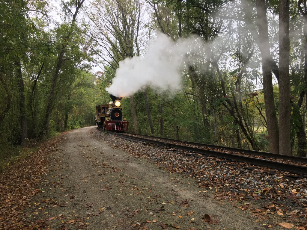 Train comes through next to York County Heritage Rail Trail. Smoke is coming out of the top.