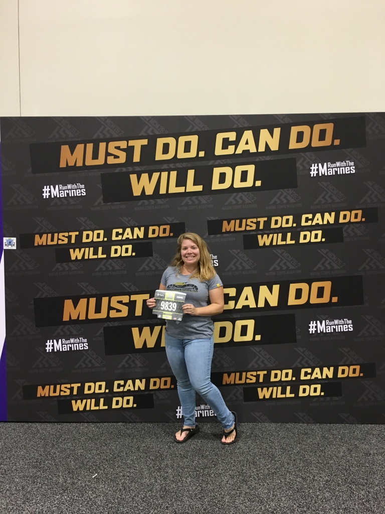 "Vanessa Junkin poses with a ""Must Do. Can Do. Will Do."" backdrop at the race expo."