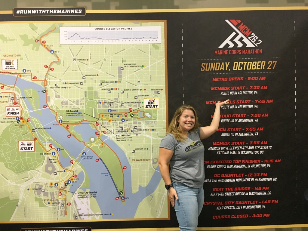 Vanessa Junkin standing next to a map of the Marine Corps Marathon course and pointing to her birthday, which is above the schedule, on a display/sign.