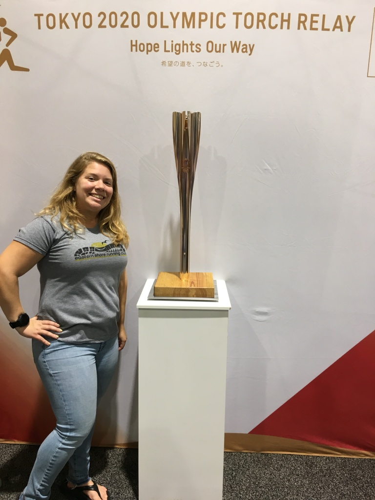 Vanessa Junkin stands by the Olympic torch.