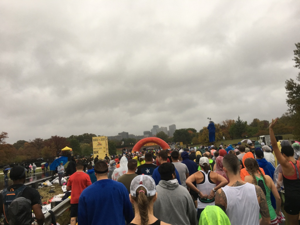 Large group of runners with the red Marine Corps Marathon circular arch and a cloudy, gray sky.