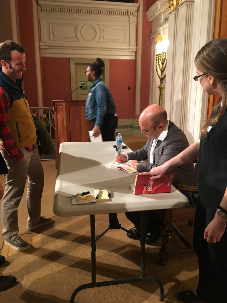 Peter Sagal sits at a table and signs a book for a fan, who is smiling.