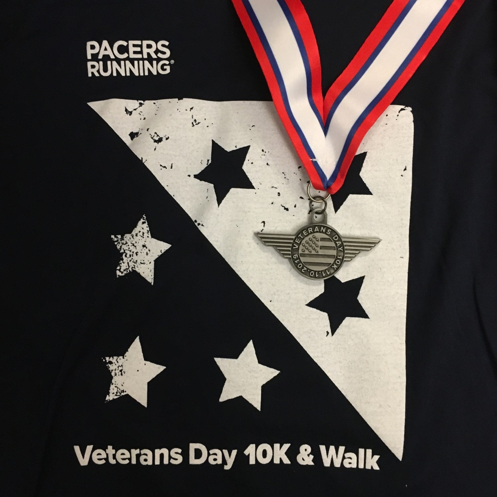 Veterans Day 10K medal against the navy blue race shirt.