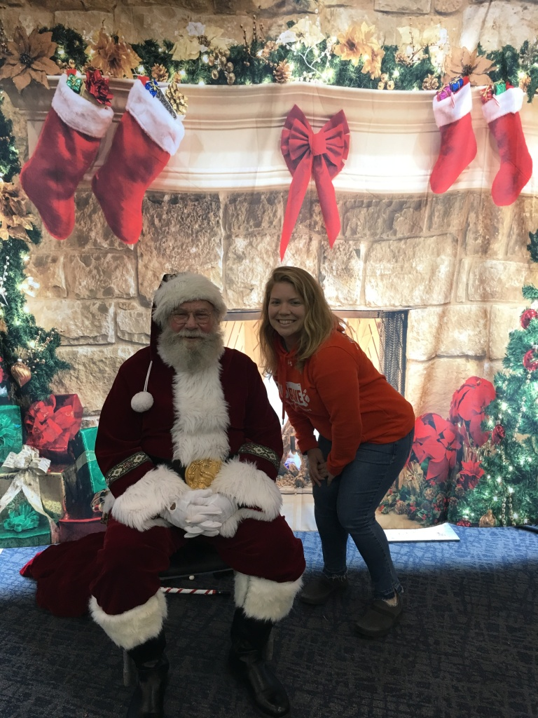 Vanessa Junkin crouching next to a sitting Santa Claus against a Christmas chimney backdrop.