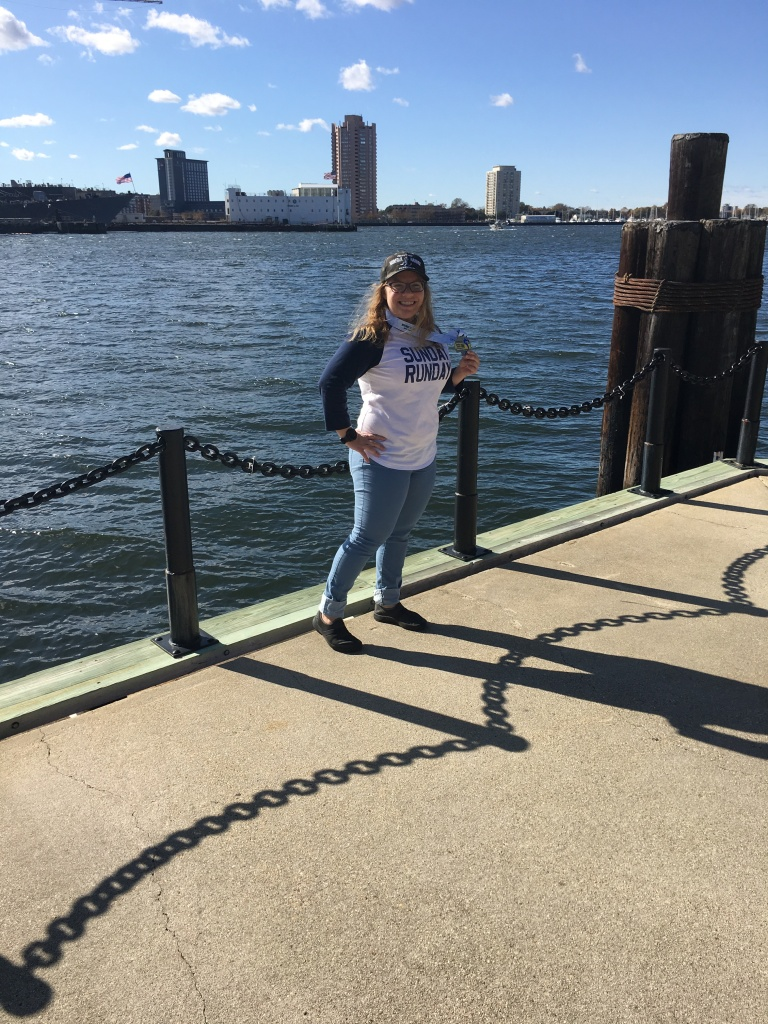 """Vanessa posing against the waterfront with her medal, wearing a """"Sunday Runday"""" shirt and the finisher hat."""