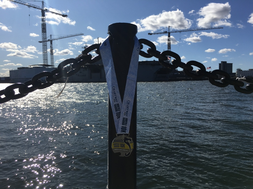 Norfolk Harbor 10K medal shown hanging on a metal pole in front of the waterfront and a ship.