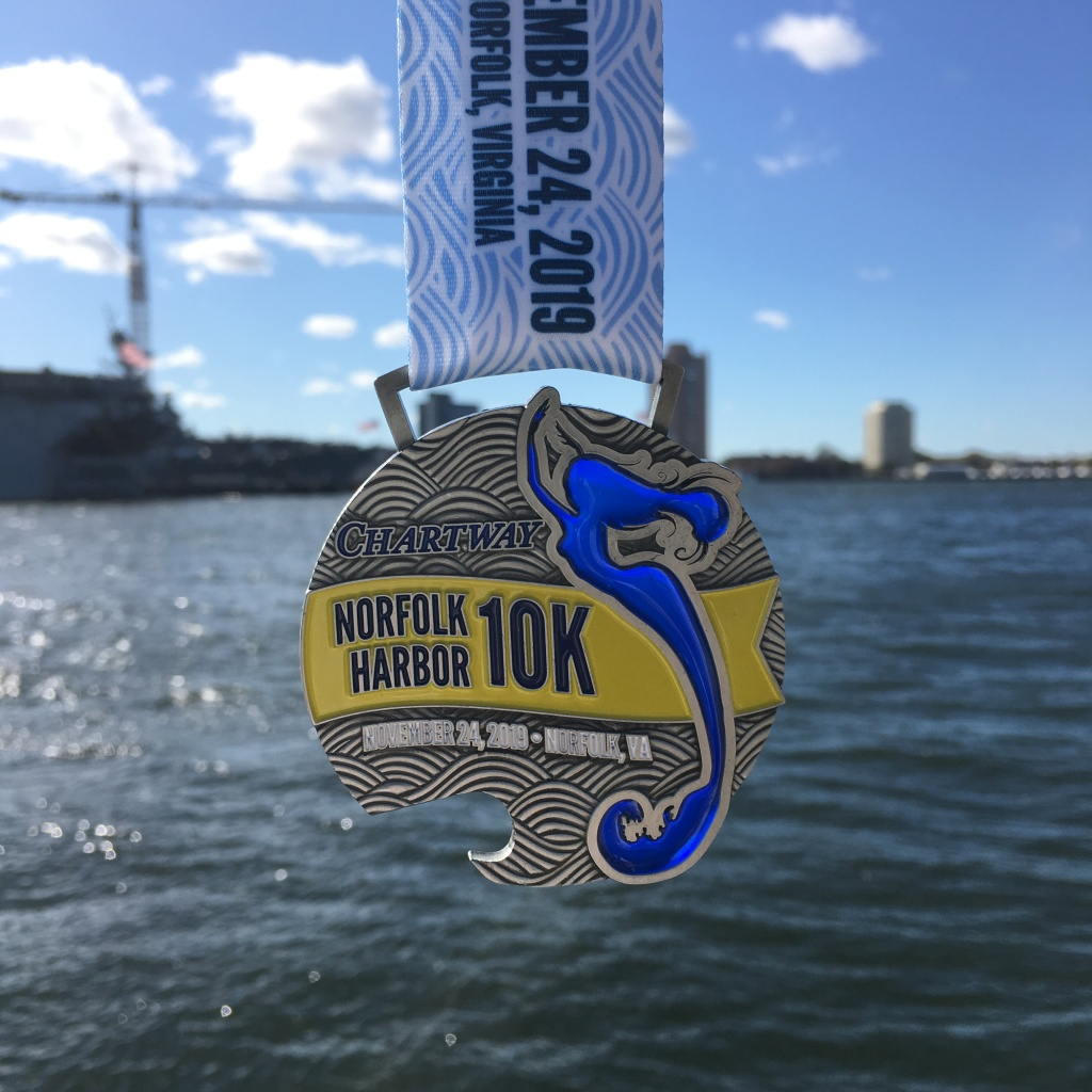 Norfolk Harbor 10K medal, shown with the light coming through a mermaid that is part of the medal.