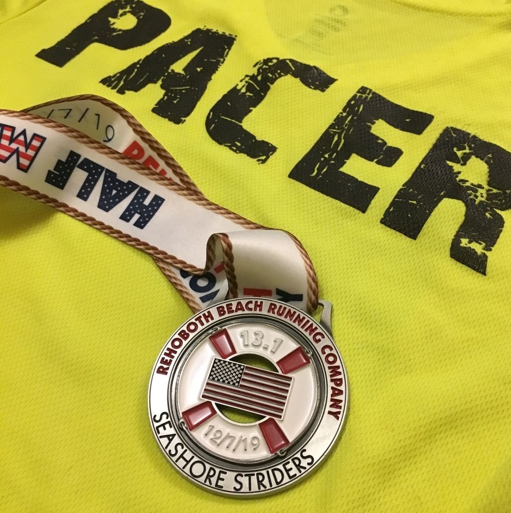 "Rehoboth Beach Seashore Half Marathon medal with the backdrop of a yellow shirt that says ""PACER."""