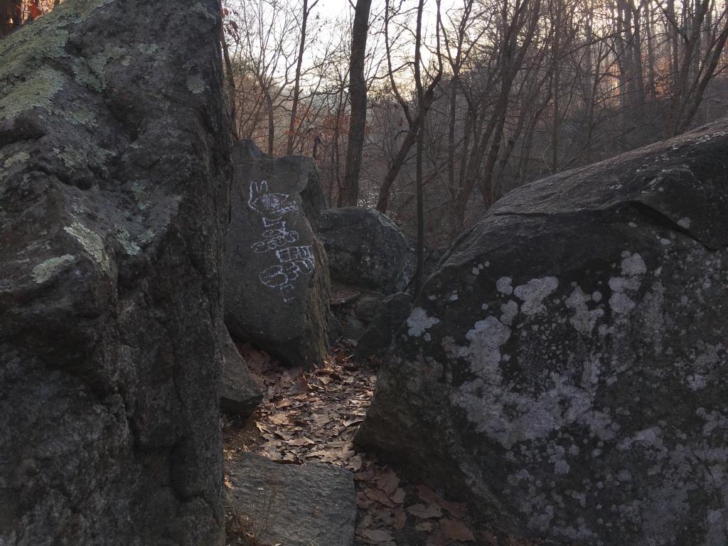 A trail goes through large rocks.