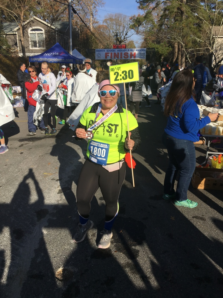 Vanessa poses with her 2:30 sign by the finish of the Rehoboth Seashore Half Marathon.