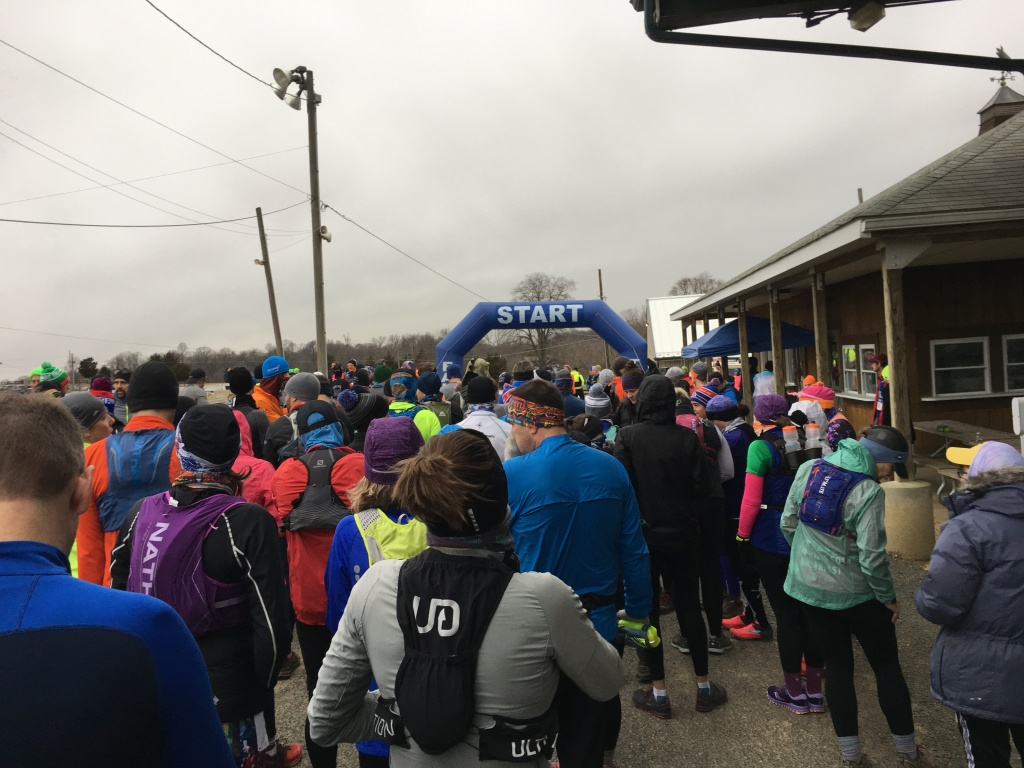 "Runners line up behind ""START"" on an inflatable blue arch."
