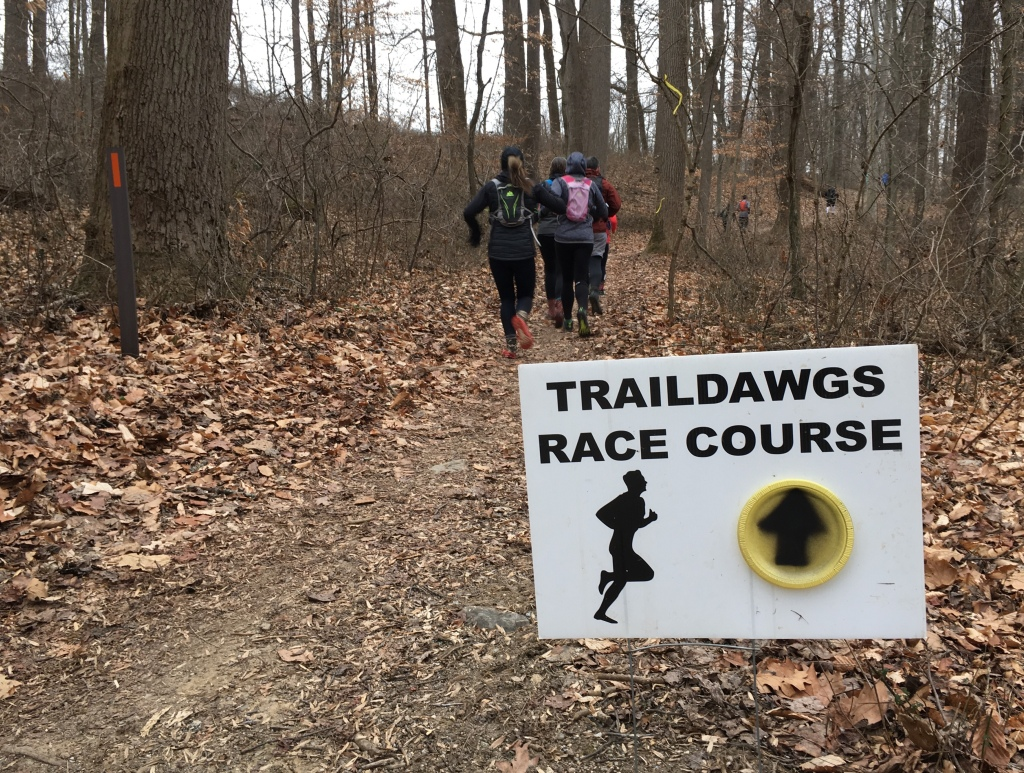 """Traildawgs Race Course"" sign in the foreground with runners on a trail behind it."