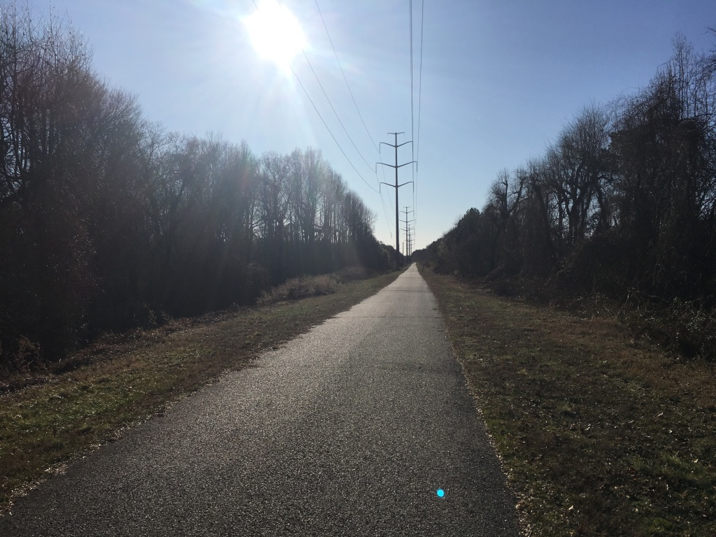 Paved trail is shown with grass and trees on both sides and power lines along the trail.
