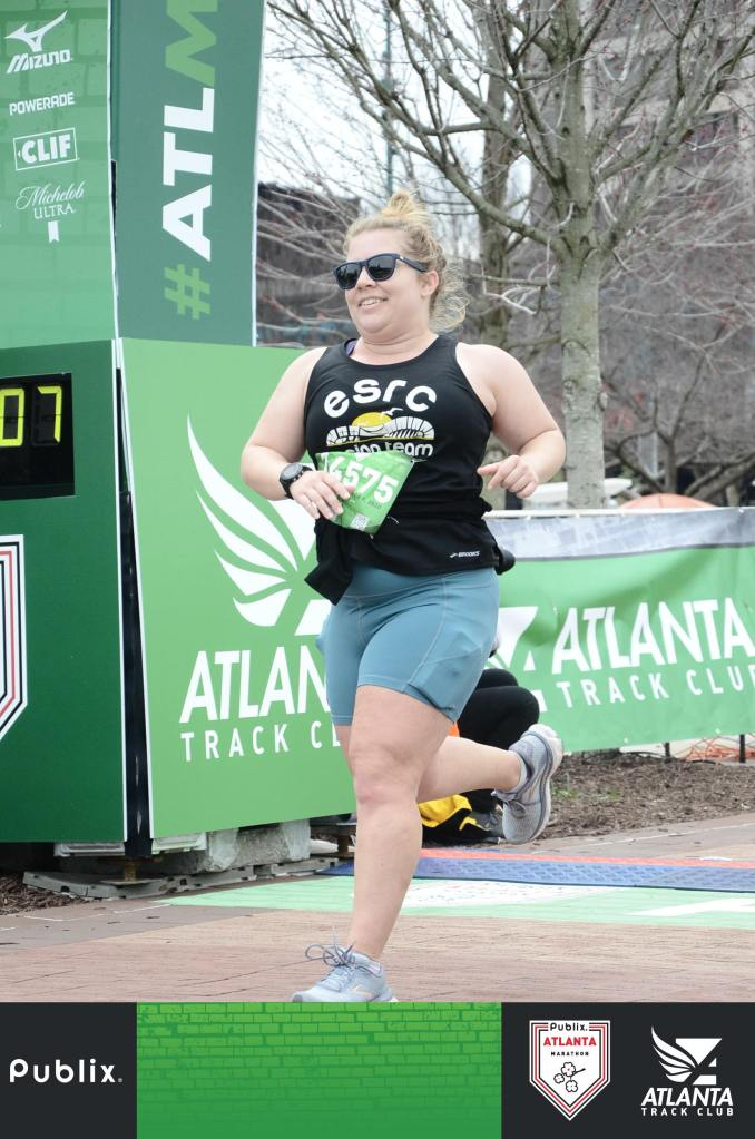 Vanessa Junkin smiles as she crosses the finish line of the Publix Atlanta Marathon.