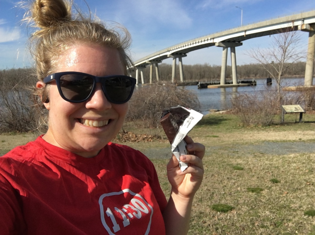 Vanessa Junkin poses with an opened Built Bar in front of the Sharptown bridge.