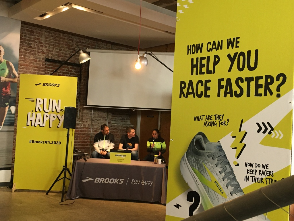 Three people at a Brooks table; pro runner Des Linden is speaking. Brooks displays are shown.