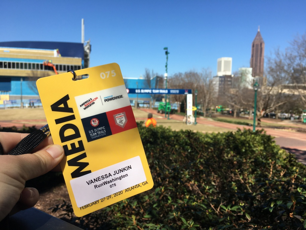 "Yellow media credential shown with Atlanta in the background, including a rectangular arch stating ""U.S. Olympic Team Trials."""