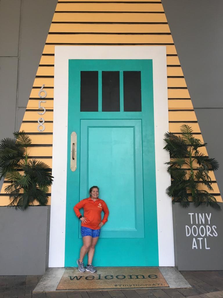 Vanessa Junkin stands in front of public art of a large door.