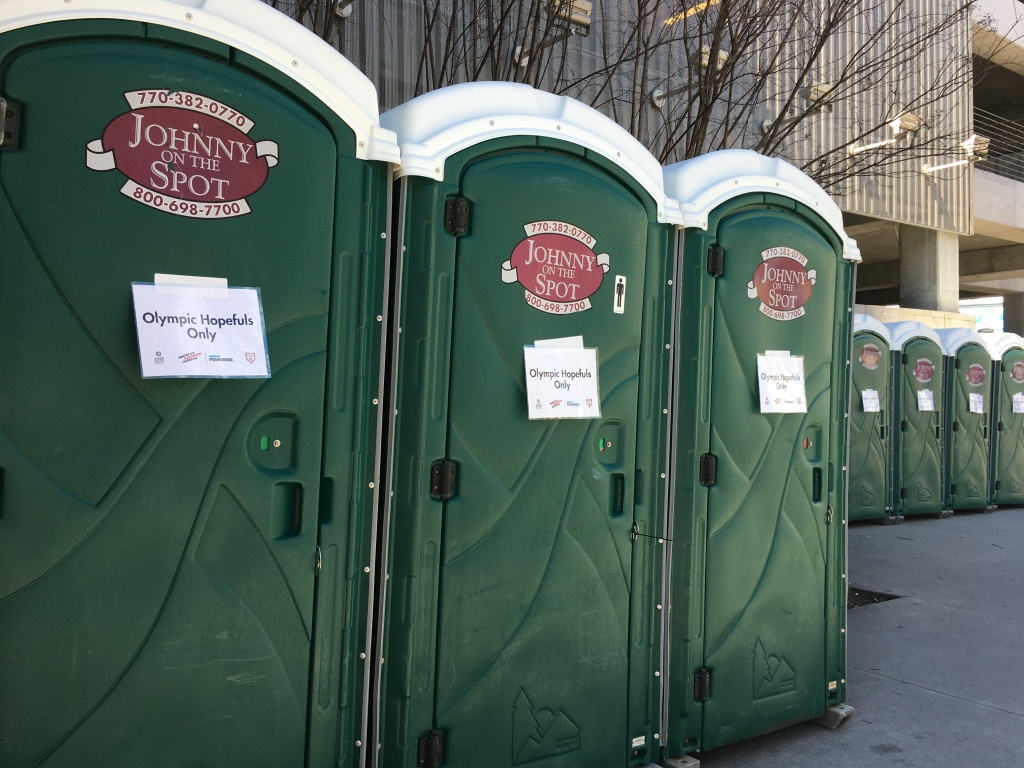 "Line of green porta-potties with ""Olympic Hopefuls Only"" signs on them."