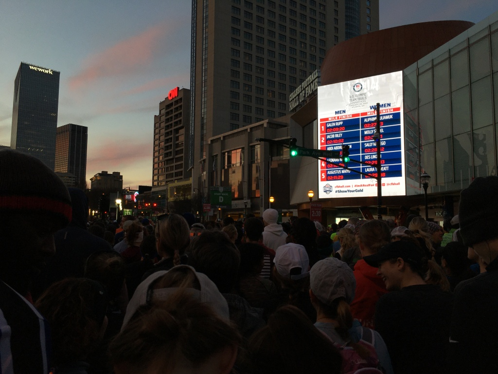 Crowd of runners waiting to start Publix Atlanta Marathon, with screen showing Top 5 men's and women's runners and times from the Olympic Marathon Trials on a screen.