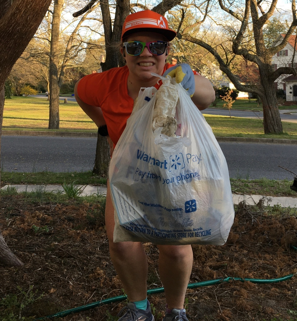 Vanessa Junkin holds out a grocery bag full of trash in front of her.