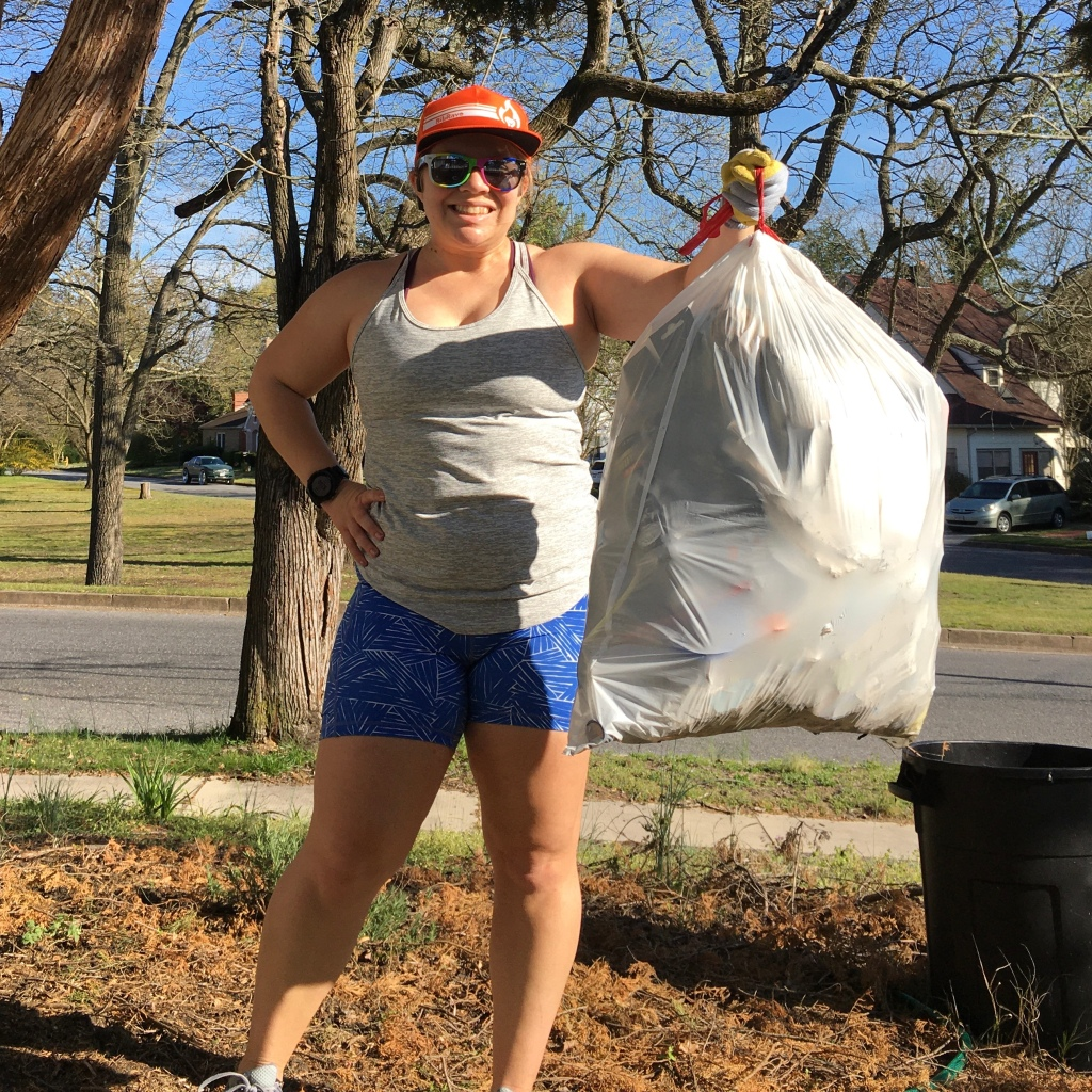 Vanessa Junkin poses standing up and holding full trash bag.
