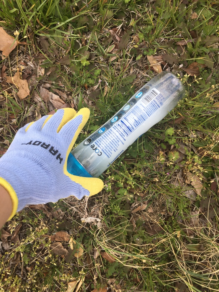Gloved hand picking up bottle in grass.