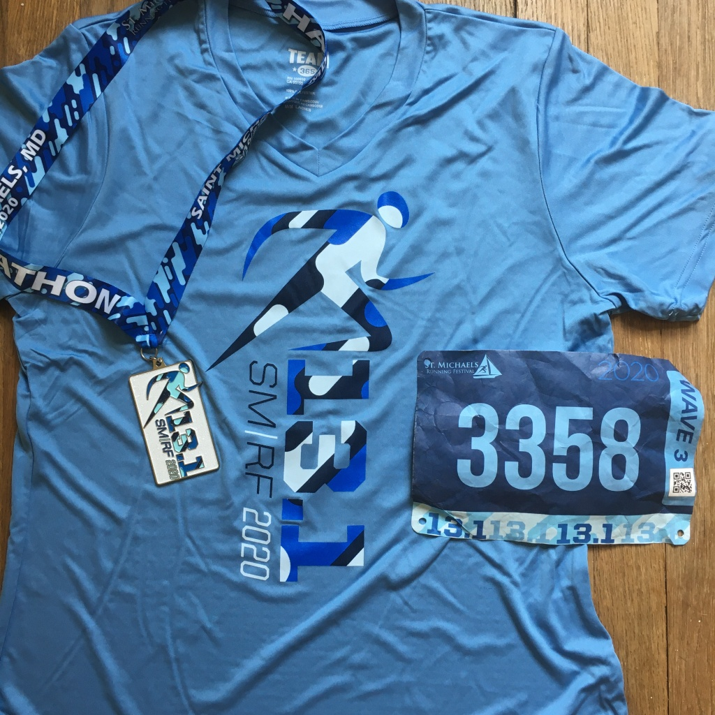 Light blue St. Michaels Running Festival running shirt with the 13.1 medal to the left and a blue bib to the right.