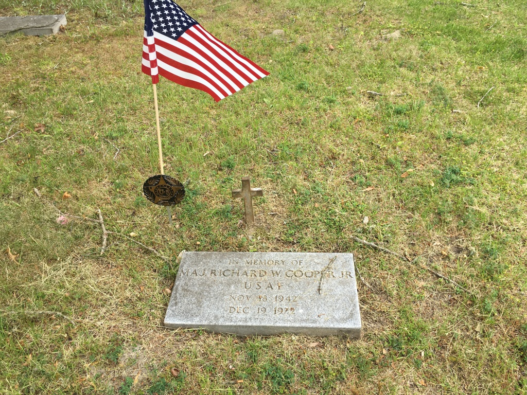 Marker with a small cross behind it and American flag near it. The marker reads:  In Memory Of Maj. Richard W. Cooper Jr.  USAF Nov 18 1942 Dec 19 1972